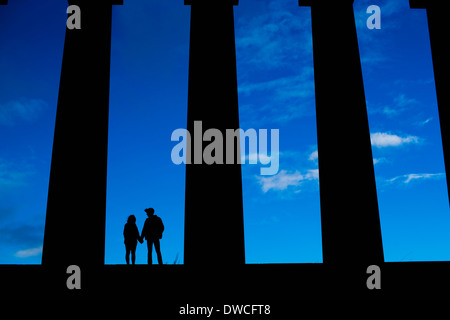A young couple hold hands on the National Monument of Scotland on Calton Hill in Edinburgh - Stock Photo