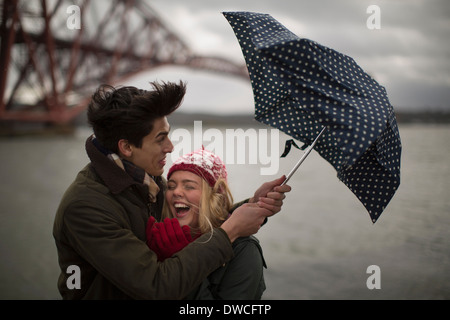 A young couple struggle with an umbrella in front of the Forth Rail Bridge in Queensferry, near Edinburgh, Scotland - Stock Photo