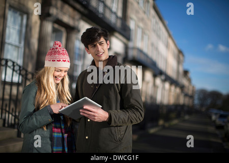 A young couple walk on Regent Terrace in Edinburgh Scotland and look at their tablet computer - Stock Photo