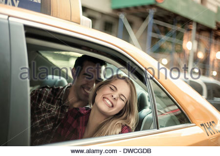 Young couple laughing in yellow cab, New York City, USA - Stock Photo
