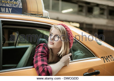 Young woman looking out from yellow cab, New York City, USA - Stock Photo