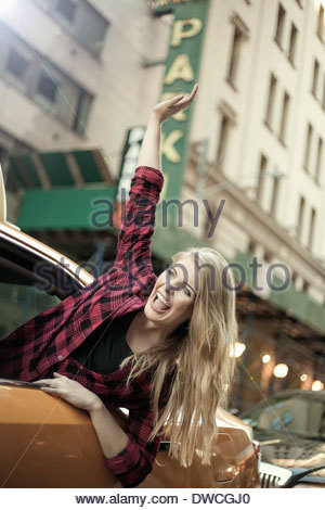 Young woman waving out from yellow cab, New York City, USA - Stock Photo