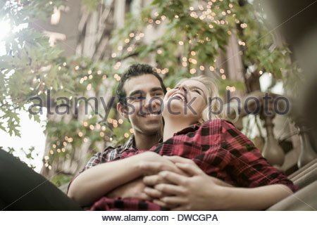 Romantic young couple sitting on steps - Stock Photo