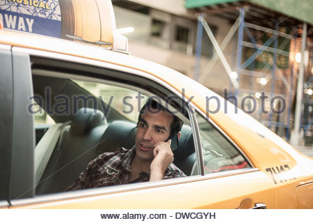 Young man using cellphone in yellow cab, New York City, USA - Stock Photo