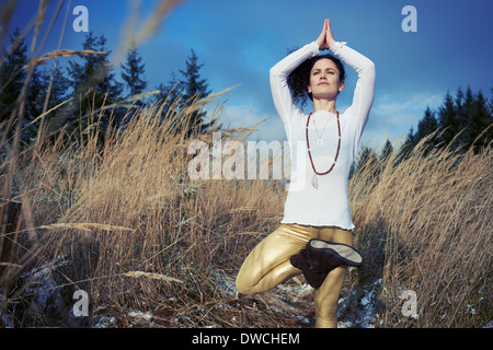 Mid adult woman doing standing tree yoga pose in forest - Stock Photo