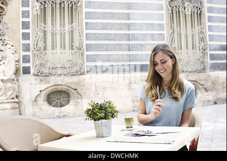 Young woman having a coffee outside Museum of Ceramics, Valencia, Spain - Stock Photo