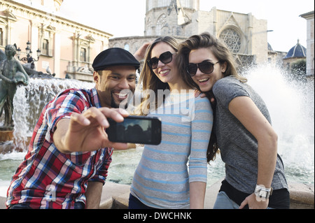 Tourist friends taking self portrait, Plaza de la Virgen, Valencia, Spain - Stock Photo