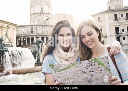Two female tourists looking at map, Plaza de la Virgen, Valencia, Spain - Stock Photo
