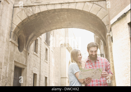 Young couple looking at map outside Valencia Cathedral, Valencia, Spain - Stock Photo