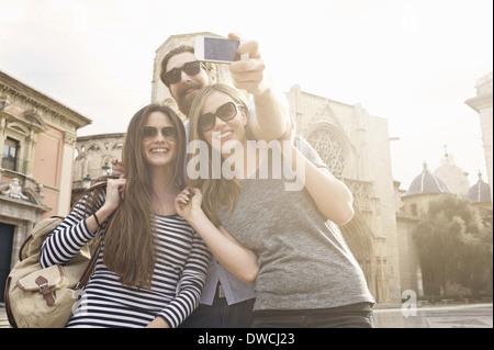 Three tourists taking self portrait, Plaza de la Virgen, Valencia, Spain - Stock Photo