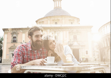 Young couple having coffee in sidewalk cafe, Plaza de la Virgen, Valencia, Spain - Stock Photo