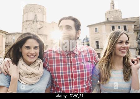 Three young tourists, Plaza de la Virgen, Valencia, Spain - Stock Photo