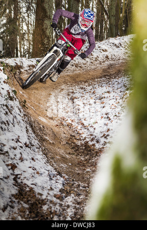 Young female mountain biker riding a forest dirt track - Stock Photo