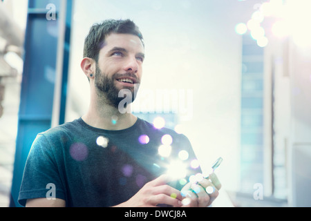 Mid adult man looking up at lights coming from smartphone - Stock Photo