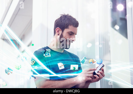 Mid adult man with apps and lights coming from smartphone - Stock Photo