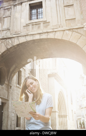Young woman looking at map outside Valencia Cathedral, Valencia, Spain - Stock Photo
