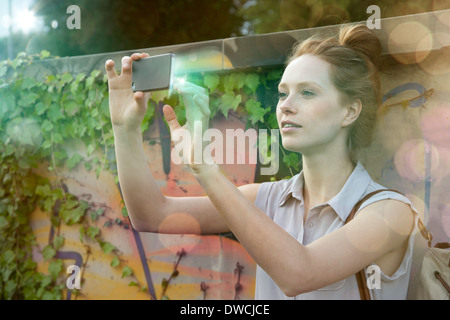 Young woman photographing self on illuminated smartphone - Stock Photo