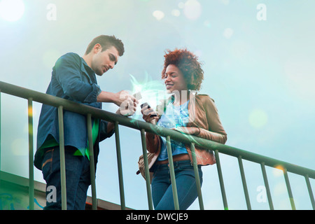 Young couple using smartphones with glowing lights coming out of them - Stock Photo
