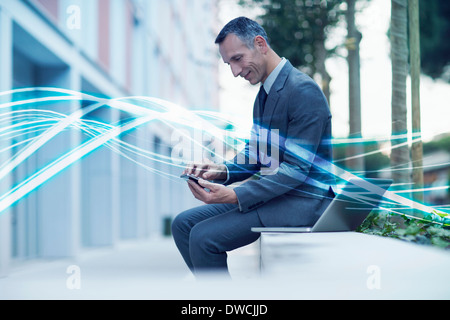 Waves of blue light and businessman texting on smartphone - Stock Photo