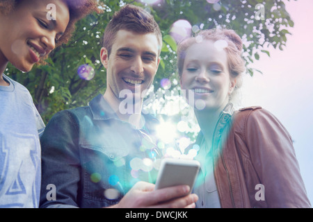 Three friends looking at smartphone with lights coming out of it - Stock Photo