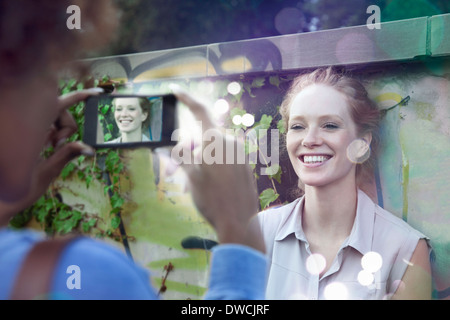 Two young women photographing using smartphone with lights coming out - Stock Photo