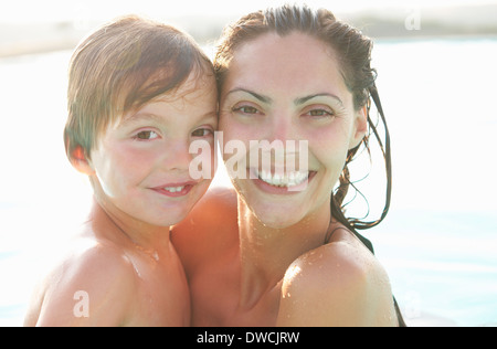 Portrait of mother and son in outdoor swimming pool - Stock Photo
