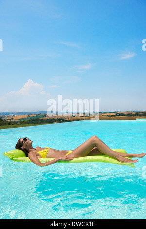 Mid adult woman lying on inflatable mattress in swimming pool - Stock Photo