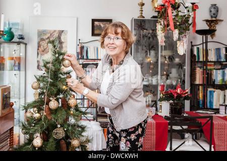 Senior adult woman decorating Christmas tree - Stock Photo