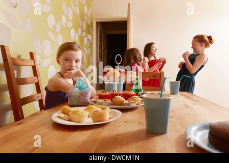 Girl at table with party food, friends in background - Stock Photo