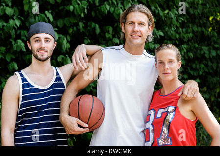 Portrait of three basketball players in park - Stock Photo