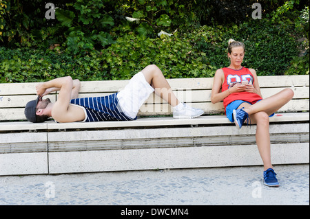 Two basketball players taking a break on park bench - Stock Photo