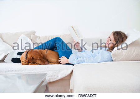 Young woman relaxing with her dog on sofa - Stock Photo