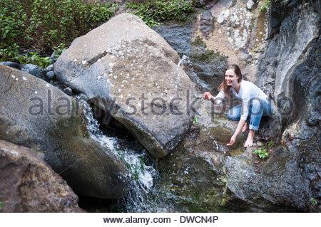 Mid adult woman crouching on rocks near waterfall - Stock Photo