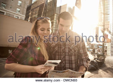 Young couple looking at maps, New York City, USA - Stock Photo