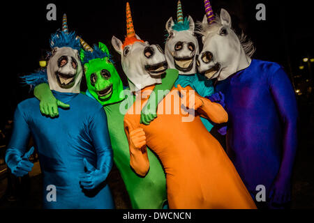 Sitges, Spain. March 4th, 2014: Bystanders in unicorn costumes dance while they follow the carnival parade in Sitges. - Stock Photo