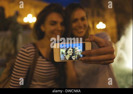 Two young women posing for self portrait, Plaza de la Virgen, Valencia, Spain - Stock Photo