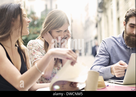 Three tourist friends enjoying a break at sidewalk cafe, Valencia, Spain - Stock Photo