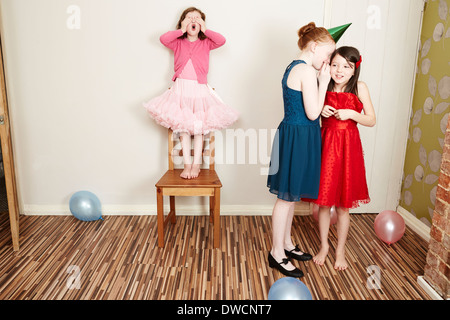 Three girls playing hide and seek at birthday party - Stock Photo