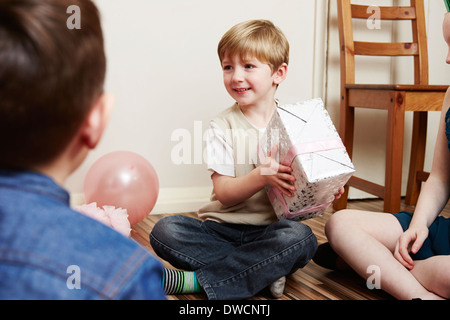 Children at party, boy holding birthday present - Stock Photo