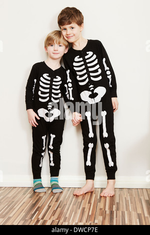 Two boys dressed in skeleton outfits - Stock Photo