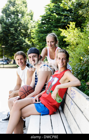 Portrait of four basketball players taking a break in park - Stock Photo