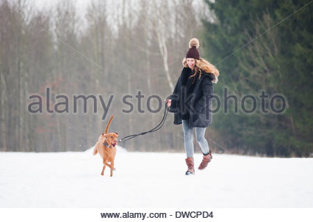 Young woman running with her dog in snowy field - Stock Photo