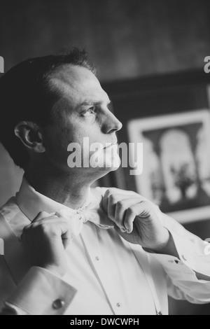 Groom tying his bow tie - Stock Photo