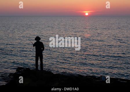 Fisherman on the coast of the Gulf of Thailand at sunset, Koh Kood, Thailand - Stock Photo