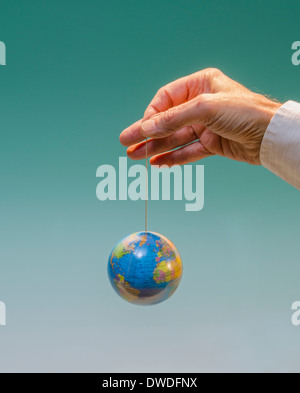 hand with dangling globe with Atlantic Ocean prominent - Stock Photo