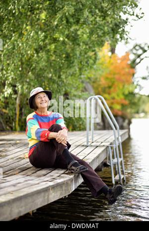 Thoughtful senior woman sitting on pier - Stock Photo
