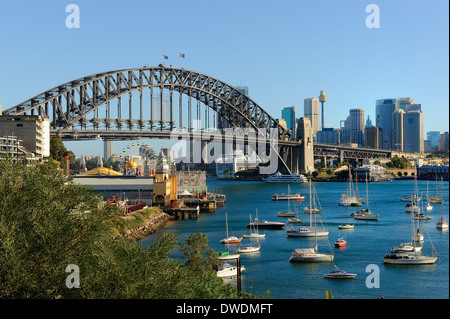 The Harbor Bridge of Sydney Australia and harbor showing Luna Park and small boats. - Stock Photo