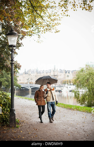 Young couple with umbrella walking on street during autumn - Stock Photo