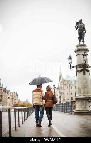 Rear view of young couple with umbrella walking on bridge - Stock Photo
