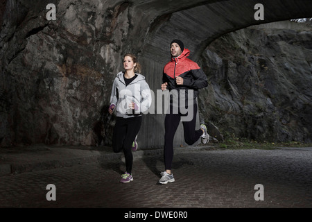 Sporty couple jogging in tunnel - Stock Photo